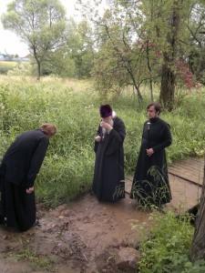 Владыка Евлогий пробует воду из источника преп. Евфросинии